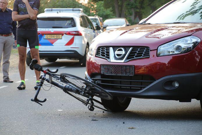 De fiets kwam klem te zitten onder de auto