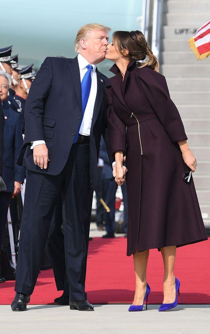 Een unicum: Donald Trump zoent zijn vrouw Melania bij aankomst in Osan, Zuid Korea. Foto Jim Watson