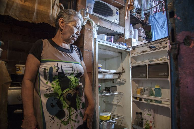 A woman shows the inside of her fridge in her house in Caracas, Venezuela. Beeld Photo News