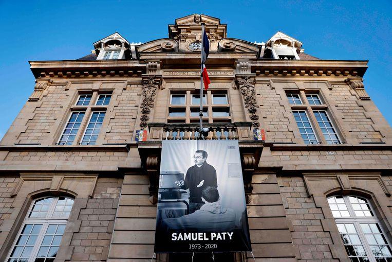Een foto van Samuel Paty in Conflans-Sainte-Honorine, na zijn onthoofding vorig jaar.  Beeld AFP