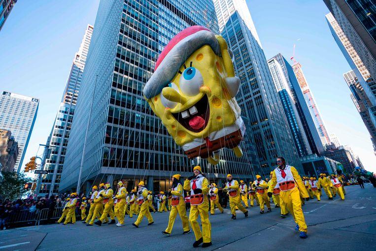 Tijdens de Thanksgiving-parade zweeft een enorme SpongeBob-ballon boven 6th Avenue in New York.  Beeld AFP