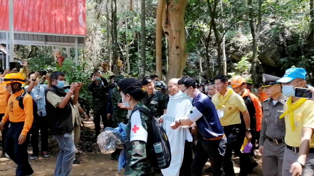 Reddingswerkers lopen samen met de 46-jarige monnik Phra Manas de Tham Phra Sai Ngam-grot uit, nadat hij daar vier dagen had vastgezeten door overstromingen.