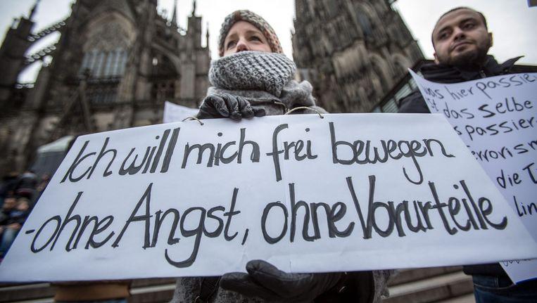 Vrouwen demonstreren in Keulen. Op het bord staat 'ik wil me vrij bewegen, zonder angst, zonder vooroordeel'. Beeld Epa