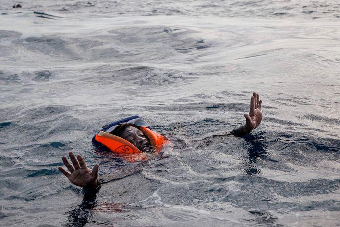 Een vluchteling probeert aan boord te komen van een schip in de Middellandse Zee. Foto Alessio Paduano