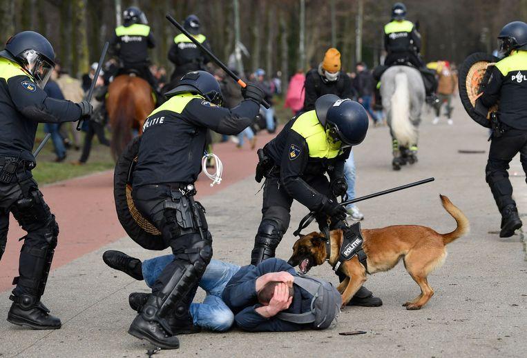 Agenten slaan op een demonstrant in tijdens het coronaprotest op het Malieveld van zondag. Beeld AFP