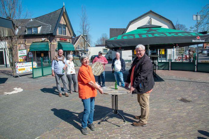 Louk Stevens en zijn vrouw zijn zo blij dat hun favoriete terras in Putten weer open mag, dat ze zelf hun tafeltje op de goede plaats willen zetten.