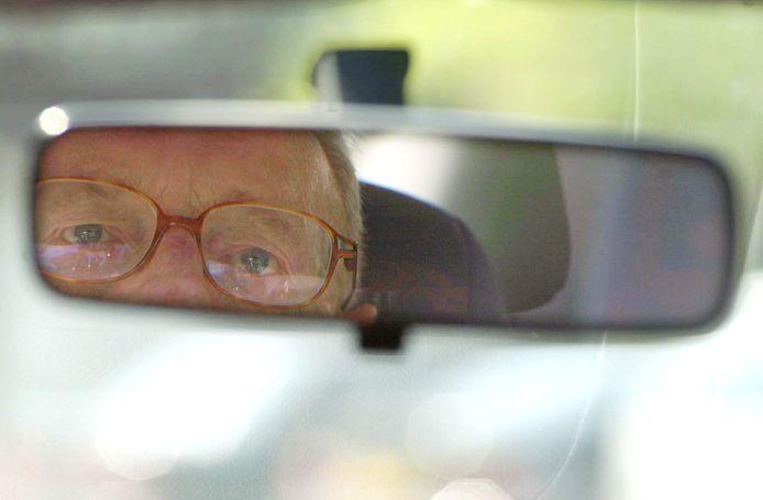 Een oudere automobilist kijkt in zijn spiegel.