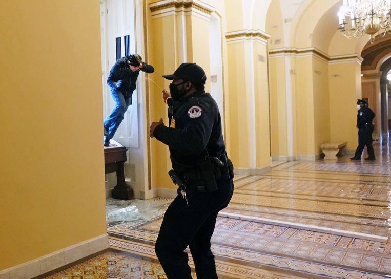 Een agent van de politie van het Capitool spuit pepperspray naar een indringer. Beeld Photo News
