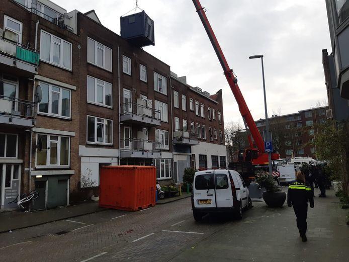 Met een hoogwerker probeert de politie ook via het dak de panden binnen te komen.
