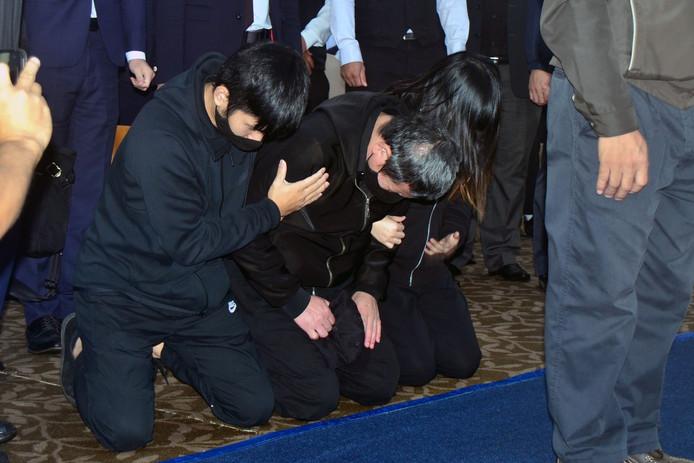 Yu Cheng-chung (midden), de machinist van de Puyuma Express die op 21 oktober ontspoorde, knielt samen met enkele familieleden van slachtoffers neer tijdens een herdenkingsdienst.