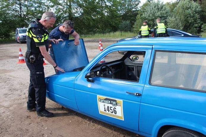 Politieman Ron Nijboer bekijkt de motor van de Reliant Rialto van Haaksbergenaar Peter Rozema bij de verkeerscontrole op de parkeerplaats bij 'Danspaleis'.