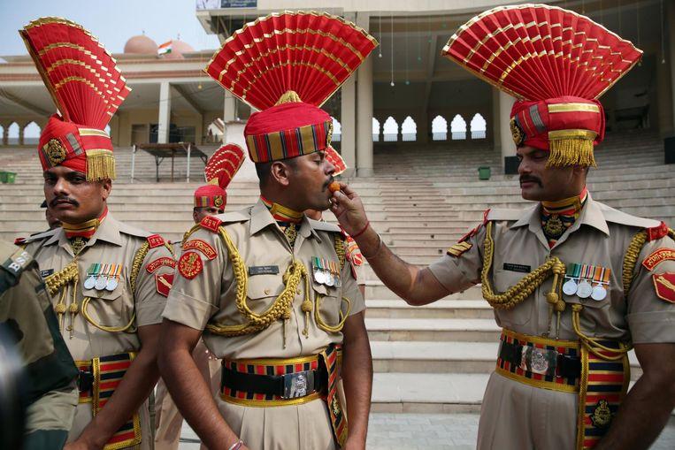 Indiase grenswachten stoppen snoep bij elkaar in de mond. Beeld epa