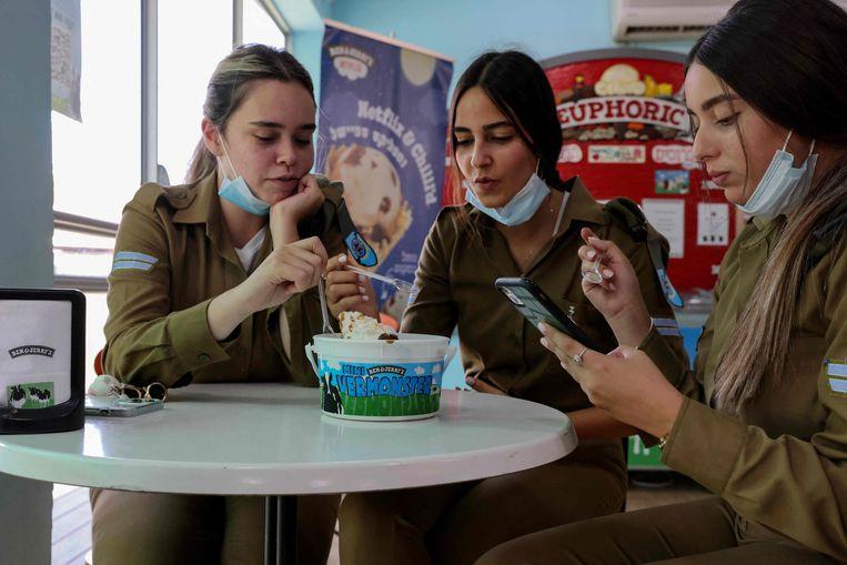 Drie Israëlische soldaten eten uit een bak met ijs van Ben & Jerry's. Beeld AFP