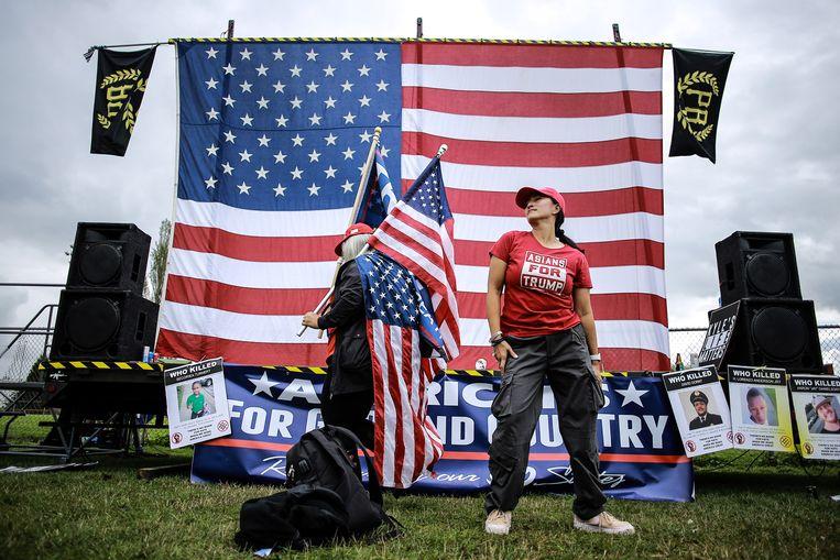 Twee vrouwen dansen voor het podium tijdens een Proud Boys-rally in Portland, Oregon. Beeld SOPA Images/LightRocket via Gett