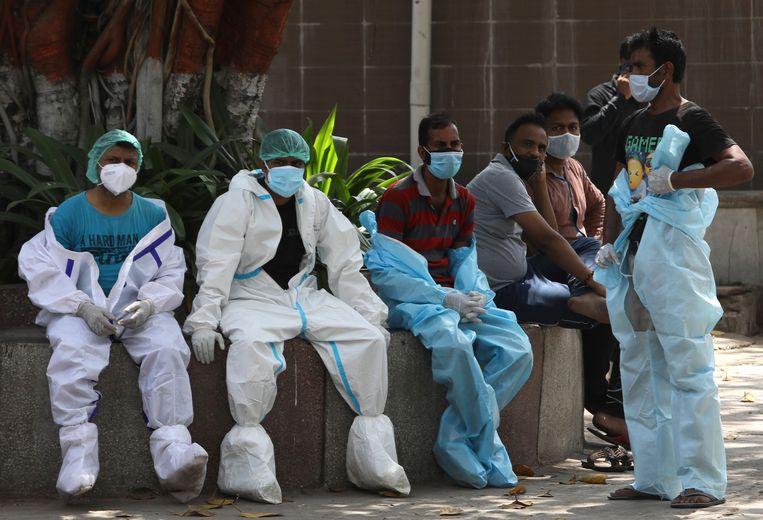 Zorgmedewerkers nemen even pauze in New Delhi, nadat ze even eerder overleden coronaslachtoffers hebben gecremeerd. Beeld AP