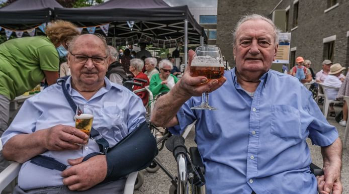 André Decavel (links) en Josef Lamon, bewoners van woon- en zorghotel Aurélys, genieten in de Grote Heerweg van de koers. En daar horen een pintje en een Kwaremont koersbiertje bij