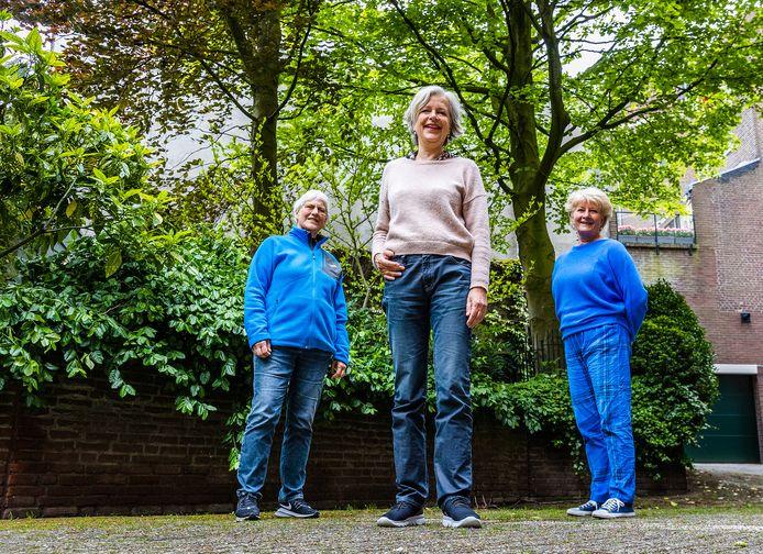 In de tuin van het atelier van vioolbouwer Lucienne van der Lans (rechts) staan Maja Kooistra (links) en Anneke van Veen (midden). Ze bewonderen de bomen in de tuin, achter hen staan een rode beuk en goudbeuk.