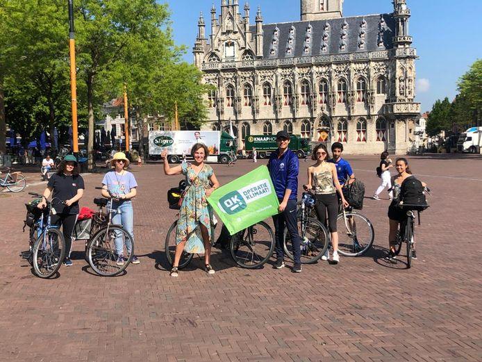 De zeven fietsers van Operatie Klimaatgroep Zeeland, onder leiding van Jacqueline de Winter (midden, met spandoek) bij het begin van hun tocht in Middelburg.