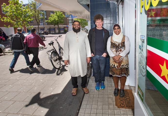 In het midden: Itai Cohn, bewoner van de Schilderswijk en organisator van tours door de wijk. Hij doet dan ook verschillende ondernemers aan zoals hier de famillie Ahmed van de winkel Food 786.