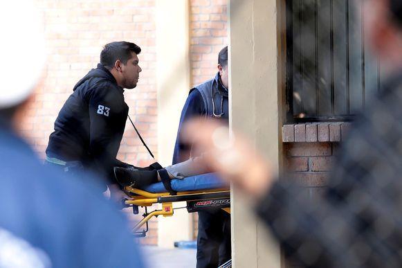 Hulpverleners dragen een persoon weg na de schietpartij.
