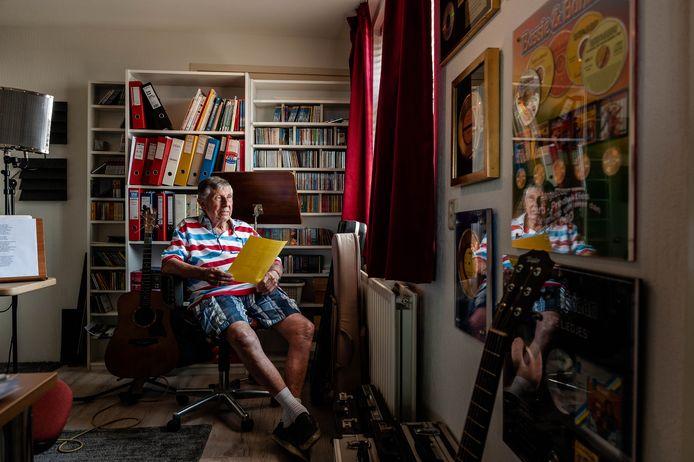 Aad Klaris in zijn studio, omringd door equipment, mappen vol liedjes, cd's en gouden platen