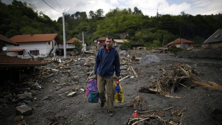 Een man in Bosnië draagt de spullen met zich mee die hij nog uit zijn verwoeste huis kon halen. Beeld reuters