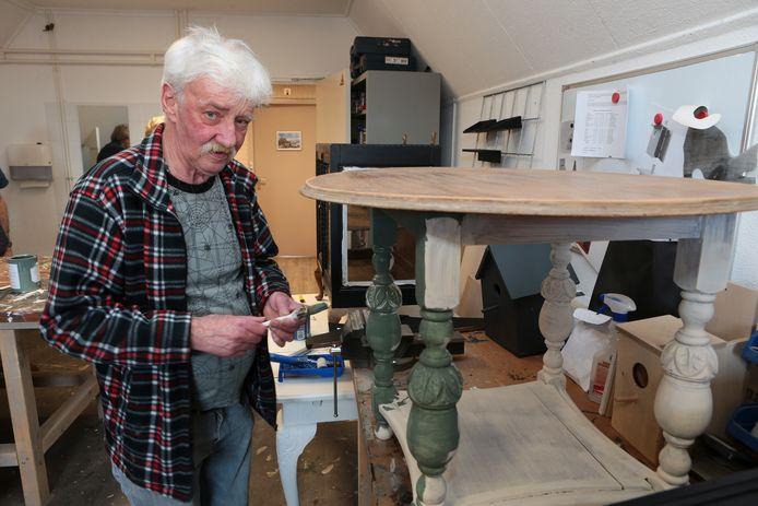 Ton, bewoner van Huize Steijndeld, werkt aan een tafeltje: ,,Het maakt me eigenlijk niet zoveel uit welke kleur het moet worden, het werk ontspant me.''