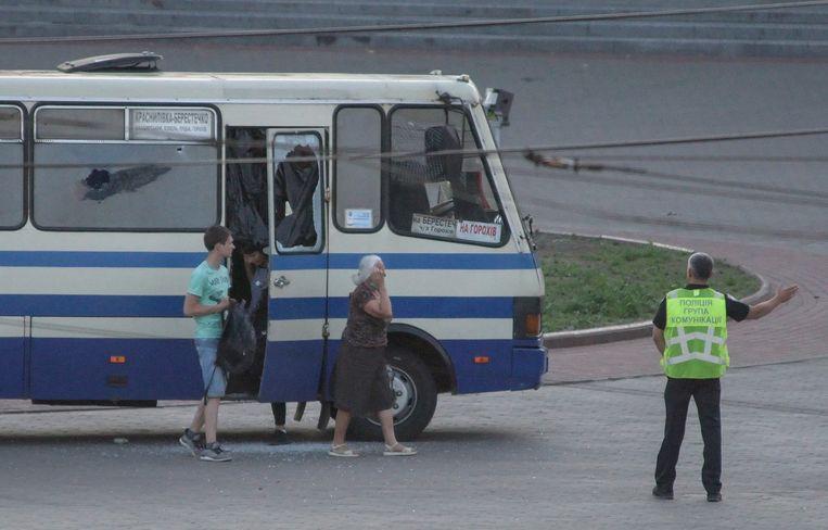Een politieman escorteert drie gijzelaars, die na urenlange onderhandelingen zijn vrijgelaten, uit de bus waarin zij werden vastgehouden.  Beeld EPA