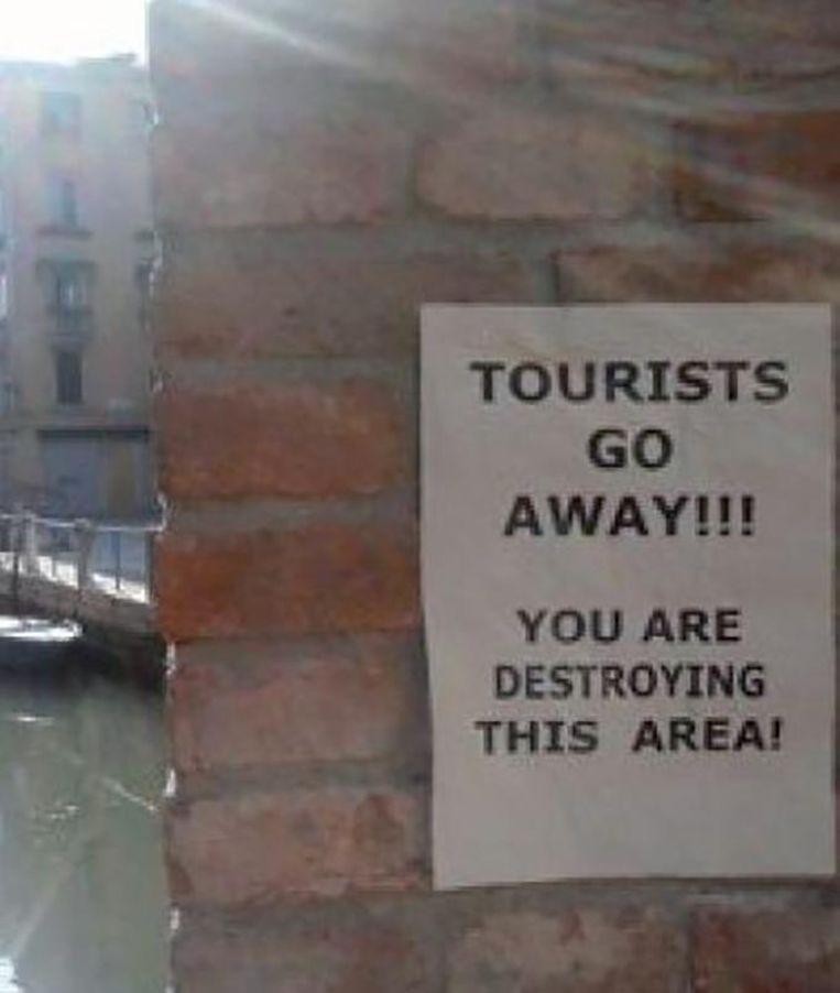 Deze posters dagen overal op in het door toeristen overspoelde Venetië. Beeld kos