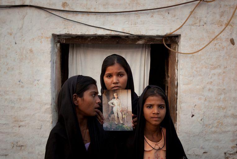 De dochters van de Pakistaanse christen Asia Bibi poseren met een foto van hun moeder voor hun uis in Sheikhupura in de Punjab provincie. Beeld REUTERS