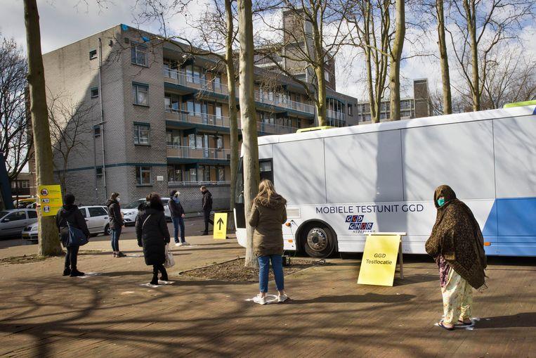 Een rij wachtenden bij de mobiele testlocatie van de GGD in Delfshaven, Rotterdam-West. Beeld Arie Kievit