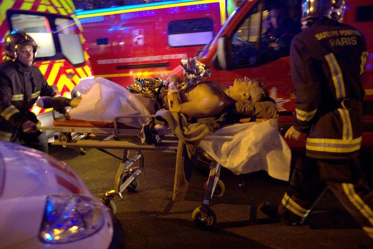 Een gewonde wordt na het bloedbad in de concertzaal Bataclan weggebracht.