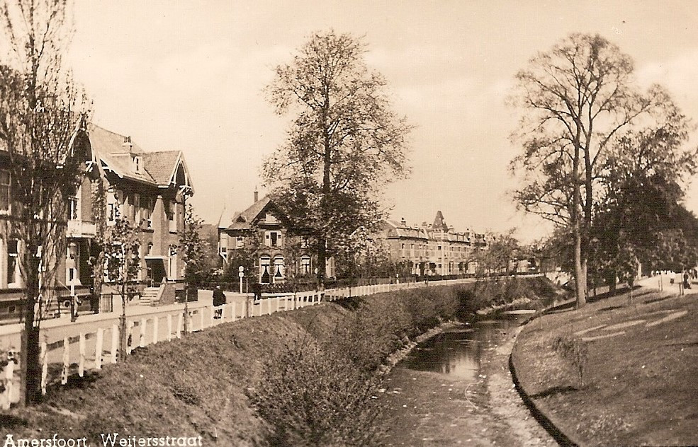 De beek kabbelt langs de Wijersstraat. De weg naar links, bij de boom midden op de foto, is de Van Persijnstraat. De beek werd hier geflankeerd door een houten hek.