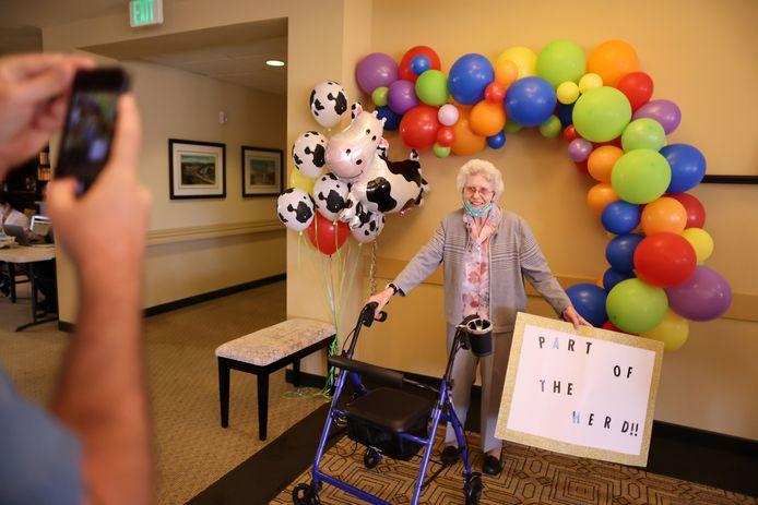 De 88-jarige Marcie Meek poseert na haar vaccinatie met een pancarte die verwijst naar groepsimmuniteit.
