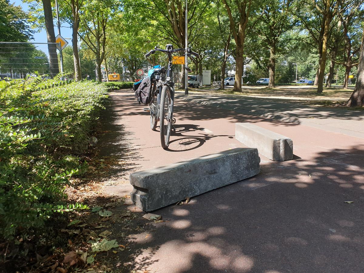 Twee betonnen stoepranden werden dwars over een fietspad in Tilburg gelegd.