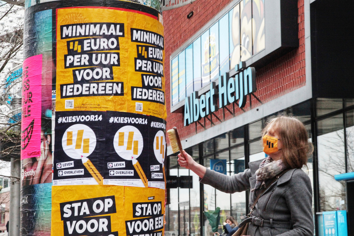 Posters plakken op een actiedag voor een minimumloon van 14 euro per uur vanaf 1 januari 2022.