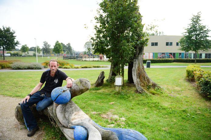 Hans Nijmeijer voor wat eens de dikste eik van Hengelo was, op een boombank, ook door hem gemaakt.