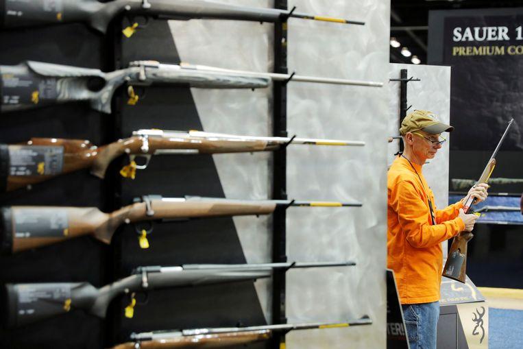 Een man inspecteert een geweer tijdens de jaarlijkse bijeenkomst van de NRA in Indianapolis. Beeld REUTERS