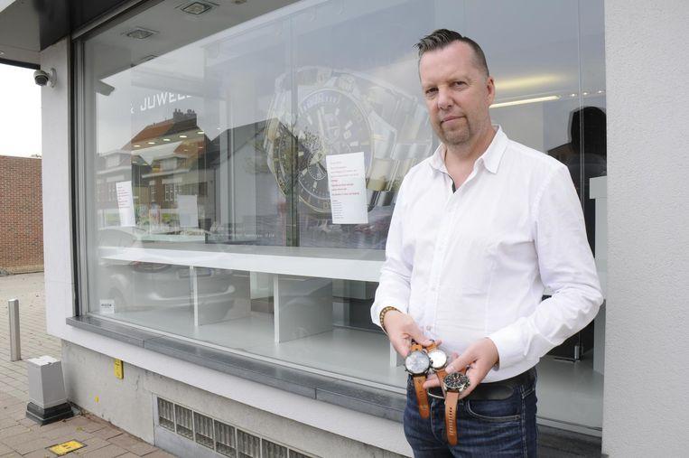 Wim Ruelens voor zijn lege etalage met enkele beschadigde uurwerken in de hand.
