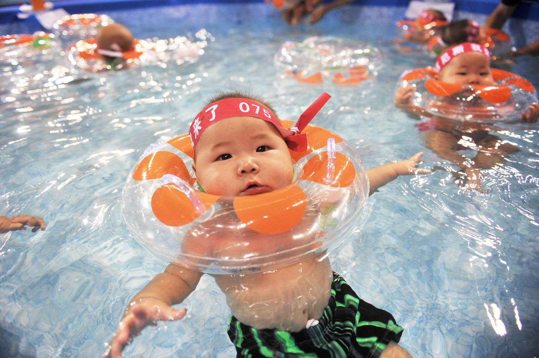Chinese baby's en hun ouders proberen het wereldrecord te verbreken van het aantal baby's dat samen zwemt. Beeld AFP