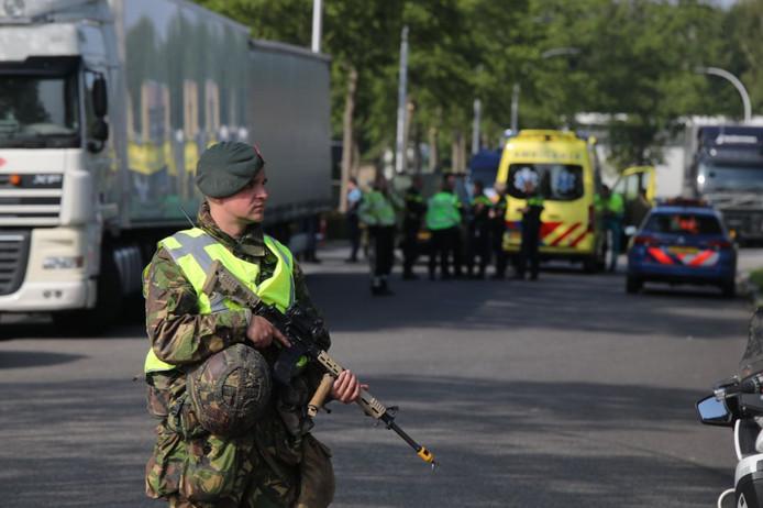 Een nog volledig 'omgehangen' militair van de Nationale Reserve bewaakt de plek van het ongeval, waarbij een vrouwelijke reserviste zwaar gewond raakte.