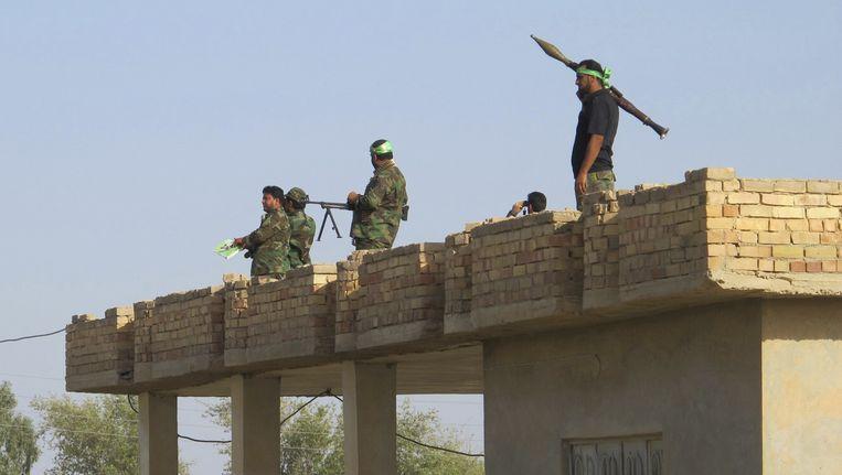 Sjiitische milities van de Mehdi Army in een buitenwijk van Tikrit. Ze vochten vandaag met het Iraakse leger om de stad Tikrit, die in handen is van IS. Beeld reuters