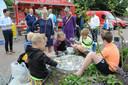 Wethouder Jacqueline van Burg (l) en landschapsontwerper Marjan van Capelle kijken toe hoe zes leerlingen van Stapelhof een schelpenkunstwerk makenop het Schelpenplein in Renesse.
