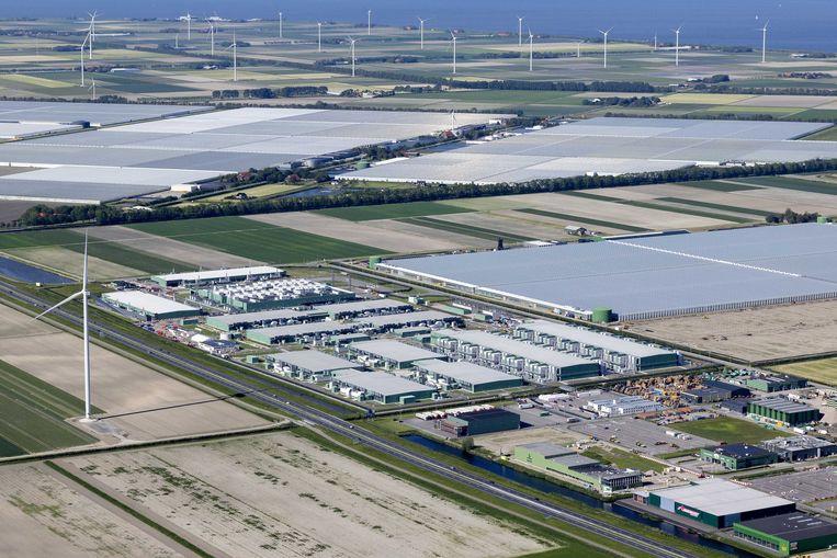 Het datacenter van Microsoft in Middenmeer, met op de achtergrond de windmolens in Wieringermeer. Datacenters van techbedrijven krijgen kritiek: ze zouden veel (groen opgewekte) energie verbruiken en het landschap ontsieren. Beeld ANP