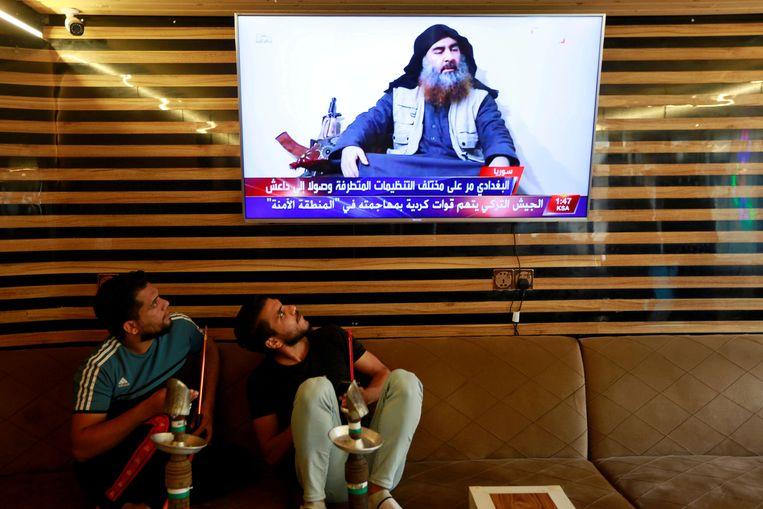 Iraakse jongeren kijken naar nieuws over de dood van Al-Baghdadi in  Najaf. Beeld REUTERS