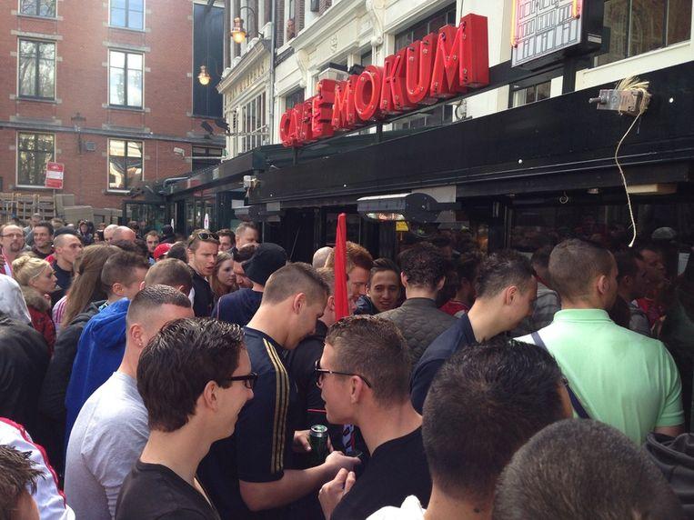 Met de gezichten tegen de ramen gedrukt proberen de fans op het Leidseplein iets van de wedstrijd mee te krijgen. Beeld Maarten van Dun