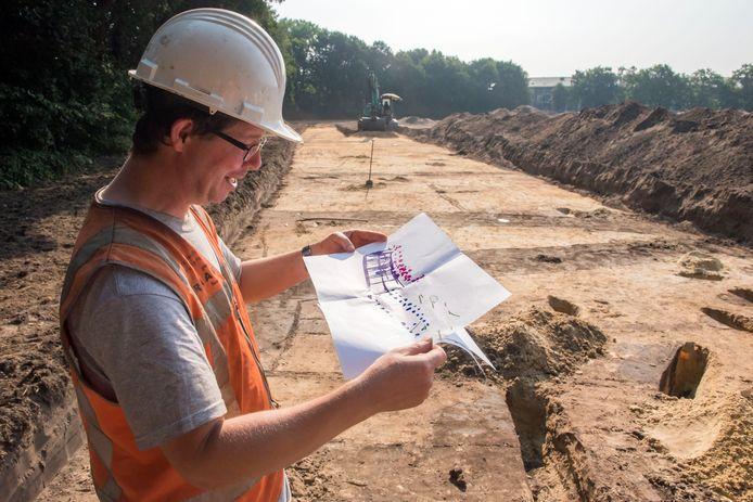 Archeoloog Eric Norde van bureau Raap toont de kaart met vondsten van twee boerderijen, die gevonden zijn in de achter hem liggende afgegraven strook van tien meter breed.