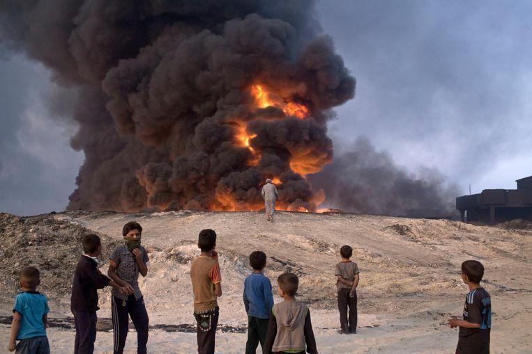 Mensen kijken naar een brandende oliebron. Beeld ap