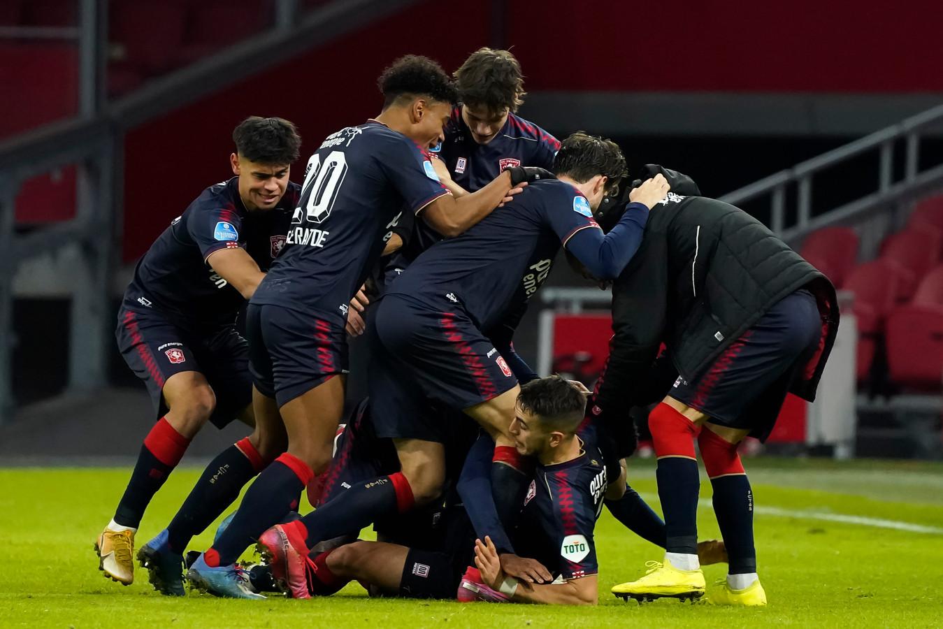 Queensy Menig wordt bedolven onder zijn dolblije ploegmaten nadat hij de winnende voor Ajax tegen FC Twente maakte.