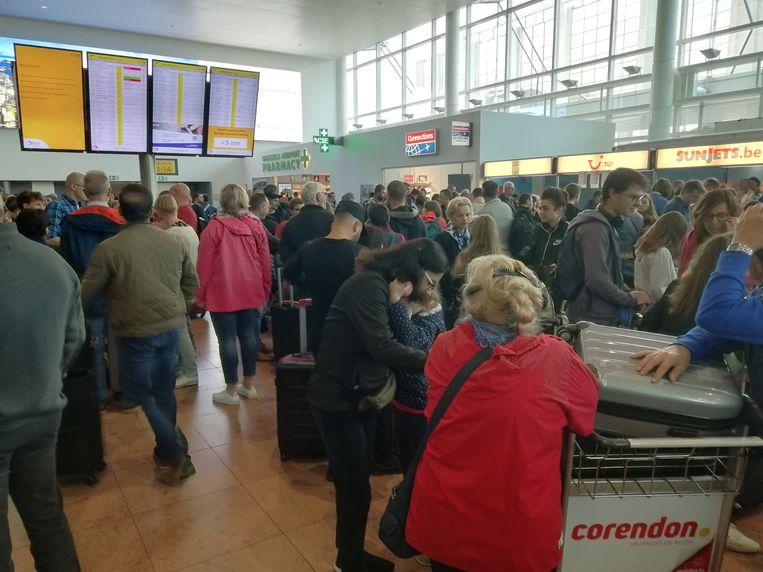 Reizigers wachten op hun bagage op Brussels Airport. Beeld BELGAONTHESPOT
